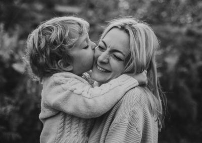 Son kissing mother, family photoshoot