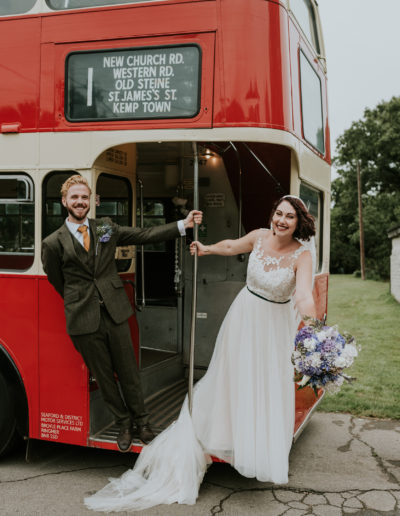 Couple on red bus, wedding day