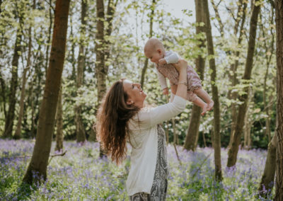 Mother holding her baby up in a bluebell wood
