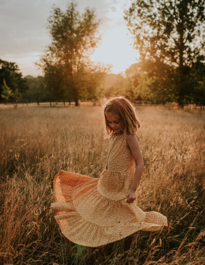 Girl twirling her dress in the long meadow grass at sunset