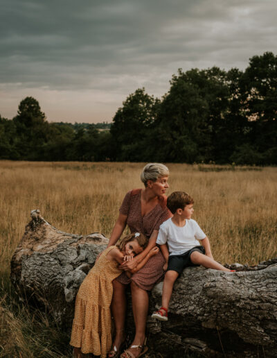 Mother and children posing on log at sunset