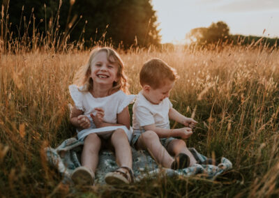 Two children laughing in the golden hour light in a beautiful wild meadow