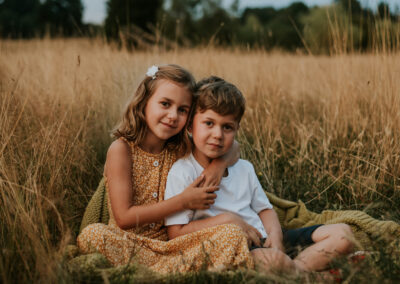 siblings hugging in the long grass, during a family photoshoot, Tunbridge Wells, Kent