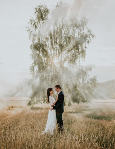 a couple pose in front of a silver birch tree with a smoke bomb in the sunlight