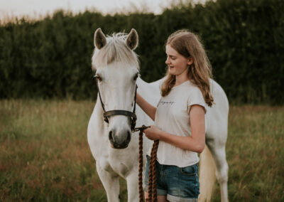 Girl posing with her white horse in a meadow