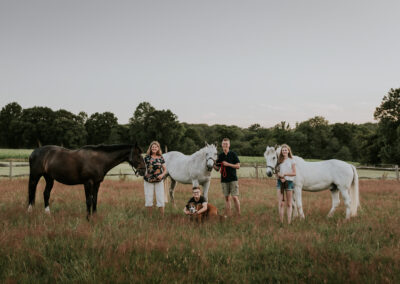 Family posing in a meadow with their horses