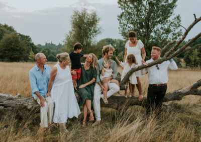 Large extended family, sitting on a log during a sunset family shoot
