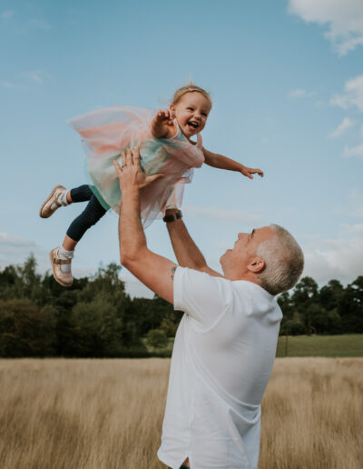 Dad throwing his daughter in the air during a sunset session