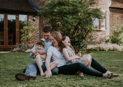 Family laughing in front of their house during family photoshoot