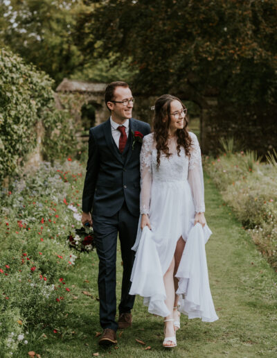 Bride and Groom walking along a grassy path