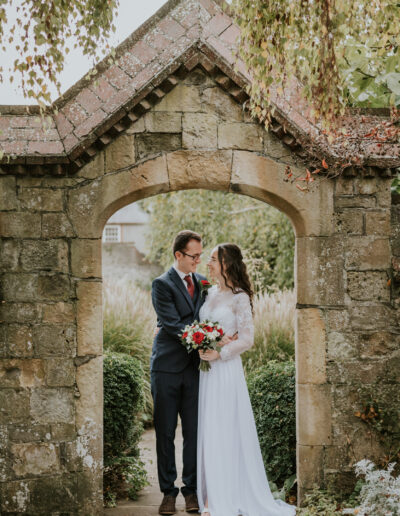 Bride and Groom standing smiling in a stone archway