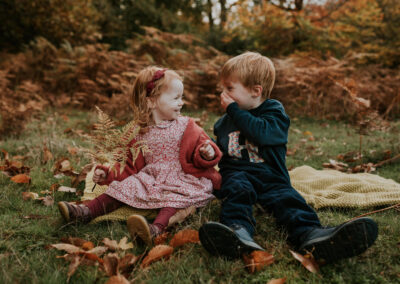 Brother and Sister laughing on a rug in the Autumn colour