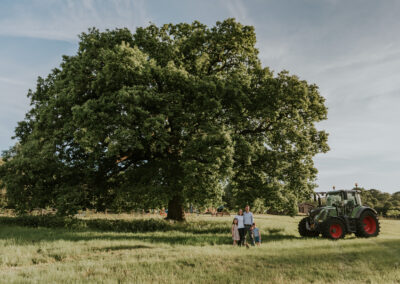 Family posing with their tractor infant of a big oak tree and their house