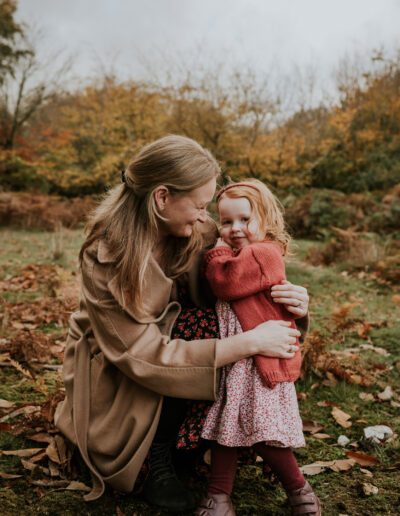 Mother hugging her daughter with Autumn colour behind them