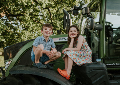 Two children posing on a tractor during a family photoshoot